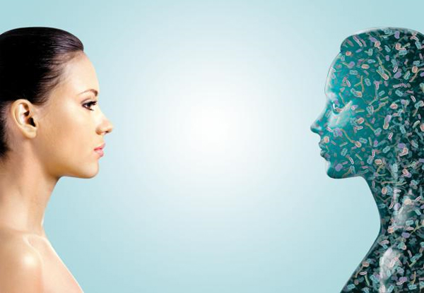 한 여성이 미생물로 가득한 얼굴을 마주 보고 있는 가상도. 우리 몸에는 인체 세포보다 10배나 많은 미생물이 산다.