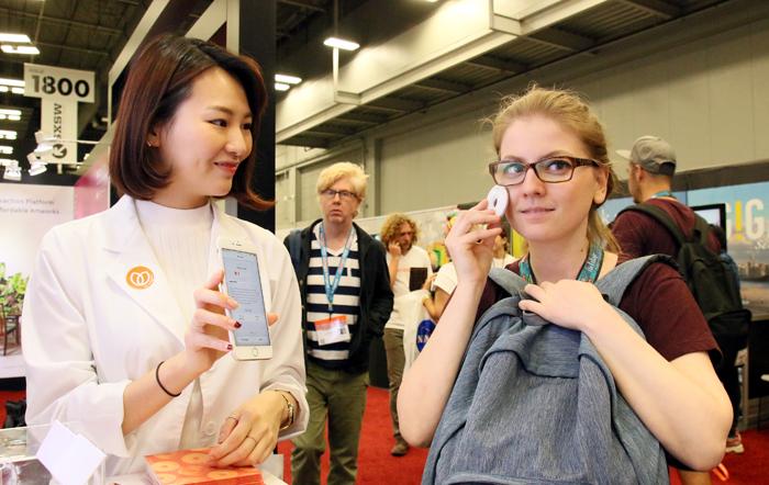 14일 미국 텍사스 오스틴에서 열린 '사우스바이사우스웨스트(SXSW)'의 IT 박람회에서 외국인이 피부 상태를 측정해 본인에게 잘 맞는 화장품을 추천해주는 한국 스타트업(창업 초기 기업) '웨이'의 서비스를 이용하고 있다.