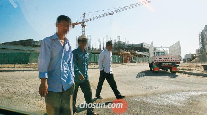 쿠웨이트의 北노동자들 2014년 12월 쿠웨이트 자흐라시(市) 외곽 신도시 건설 현장에서 북한 노동자들이 점심을 먹기 위해 숙소로 이동하고 있다. 쿠웨이트에는 5000여명의 북한 건설 노동자가 있는 것으로 추정된다. 이들은 하루 10~16시간 중노동에 시달리지만 한 달 임금은 100달러(약 11만원) 안팎인 것으로 알려졌다. 월급의 90% 정도를 상납금으로 바쳐야 하기 때문이다.
