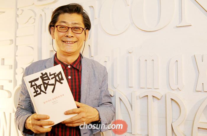 북 디자이너 정병규씨가 '치양지(致良知)―동아시아 양명학의 전개'를 들고 서 있다. 양명학의 핵심 개념 중 하나인 치양지를 책 표지에 멋진 타이포그래피로 구현했다.