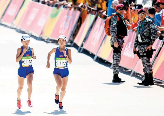 빨간 운동화가 언니, 검은 운동화가 동생 - 북한의 쌍둥이 마라토너 김혜성(왼쪽)·혜경 자매가 15일 리우올림픽 여자 마라톤 경기 결승선을 향해 나란히 달리고 있다. 출발선부터 발맞춰 달린 두 선수는 같은 기록(2시간28분36초)을 냈다. 일란성쌍둥이에 덩치도 비슷한 두 선수는 모자와 유니폼도 같은 것으로 착용해 허리에 묶은 흰색 끈(동생 김혜경)과 운동화 색깔로 구분한다.