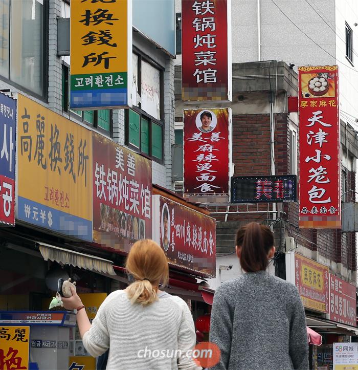 """서울의 한 대학가에 중국어 간판이 달린 음식점과 식료품점, 환전소 등이 줄지어 늘어서 있다. 국내 체류 중인 외국 유학생 약 10만명 가운데 중국인은 6만여 명으로, 중국 현지 유학원에서는 """"한국 지방 대학은 돈만 내면 갈 수 있다""""고 홍보하고 있다."""