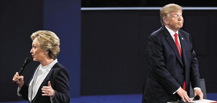 9일(현지 시각) 미국 미주리주(州) 세인트루이스 워싱턴대에서 열린 미 대선 2차 TV 토론에서 공화당 대선 후보 도널드 트럼프(오른쪽)가 방청객 질문에 답하고 있는 민주당 대선 후보 힐러리 클린턴(왼쪽)의 발언을 굳은 표정으로 듣고 있다.