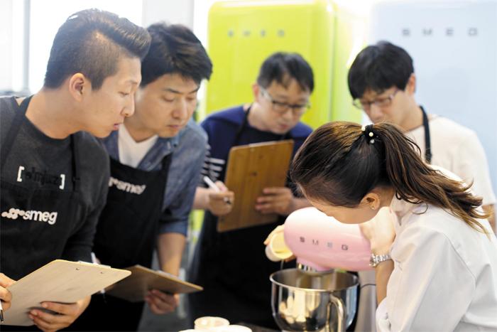 이탈리아 가전제품 브랜드 스메그에서 마련한 남성 전용 베이킹 클래스 참가자들이 강사의 제빵 반죽기 사용법 설명을 경청하고 있다.