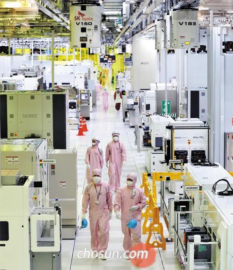 지난 21일 경기도 이천시 SK하이닉스 'M14' 공장 내 반도체 생산 라인에서 방진복을 입은 직원들이 생산 공정을 둘러보고 있다. 지난해 8월 완공된 M14는 단일 건물로는 세계 최대 규모 반도체 공장이다.
