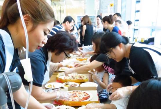미스터피자 직원들이 강원대학교 어린이병원을 방문, 어린이 환자들과 피자를 만들고 있다. /미스터피자 제공