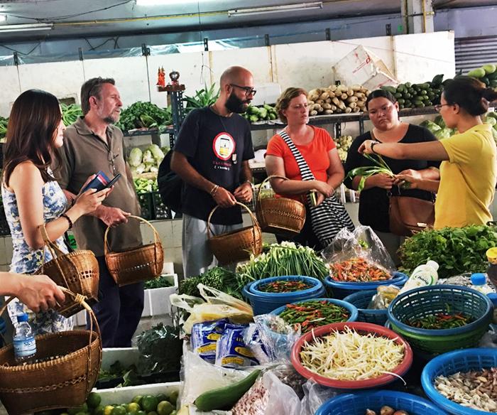 태국 로컬 시장에서 식재료 설명을 들으며 쿠킹클래스에서 사용할 재료를 구입하고 있는 여행객들.
