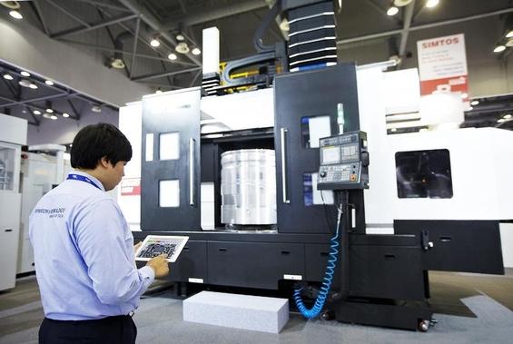 현대위아 연구원이 아이패드를 통해 CNC선반 기기를 작동시키는 모습 /현대위아 제공