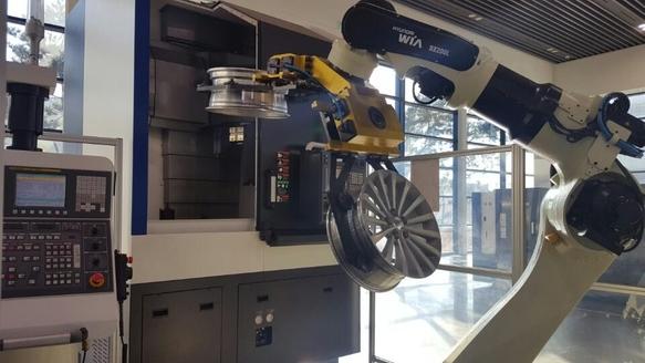 현대위아가 개발한 로봇팔 기기가 완성된 자동차 휠을 보관대로 이동시키는 모습 /박성우 기자
