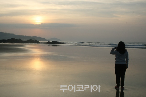 리조트 앞 해변에서 일출을 감상하고 있는 관광객