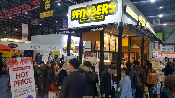 프랜차이즈 창업박람회를 찾은 관람객들이 한 브랜드의 음식을 시식하기 위해 줄을 서고 있다./윤희훈 기자