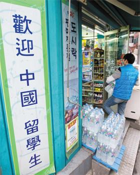 지난달 30일 서울 종로구 대학로에 있는 한 편의점에서 중국인 알바생이 생수를 옮기고 있다. 편의점 입구에 '환영 중국 유학생'이라고 쓰인 중국어 플래카드가 붙어 있다.