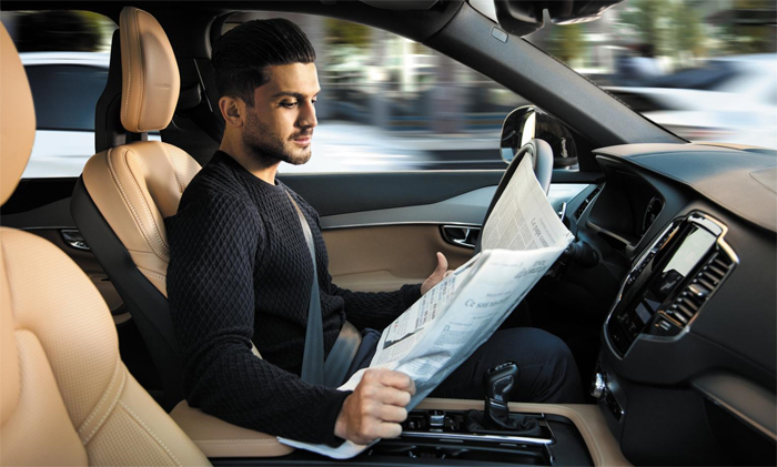 자율주행차에 탄 남성이 운전대를 놓은 채 신문을 읽는 모습. 2020년부터는 세종시 행복도시 모든 도로에서 이런 일이 가능해질 전망이다.