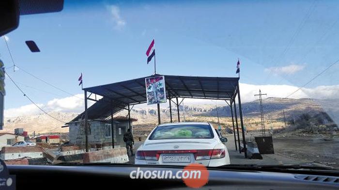 지난 13일(현지 시각) 시리아 번호판을 단 승용차가 레바논과 시리아 국경에 있는 출입국 검문소에서 검문을 받고 있다. 검문소에는 시리아 국기와 군복 차림을 한 아사드 대통령 사진이 걸려있다. 시리아 내전이 진정 국면으로 접어들면서 시리아로 들어가려는 차량이 급증했다.