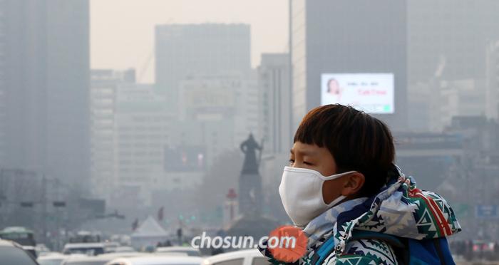 고농도 미세 먼지 현상이 이틀째 이어진 서울 시내에서 한 시민이 마스크를 쓴 채 걸어가고 있다. 지난 18일 74㎍/㎥으로 '나쁨' 수준을 기록한 서울의 일평균 초미세 먼지(PM 2.5) 농도는 19일 더 치솟아 81㎍/㎥(오후 4시 기준)까지 올랐다.