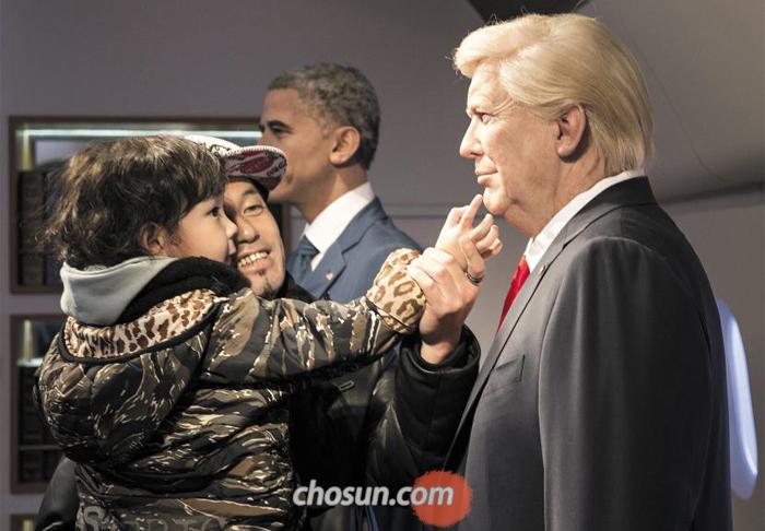 지난 9일 서울 중구 그레뱅뮤지엄을 찾은 어린이 관람객이 도널드 트럼프 미국 대통령의 밀랍인형을 신기한 듯 쓰다듬고 있다. 트럼프 인형 뒤로 버락 오바마 전 대통령이 보인다.