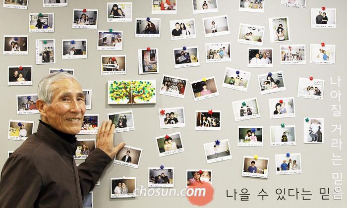 서울 성북구 한국백혈병어린이재단에서 퇴직 우체부인 문금용씨가 소아암 완치 어린이들의 사진이 걸린 게시판을 살펴보고 있다. 세 아들을 먼저 하늘로 떠나보낸 문씨는 재단에 환자 6명의 치료비를 전액 지원했다.
