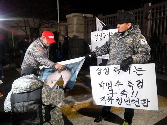 자유청년연합 회원들이 박영수 특검의 사진을 찢고 있다. /윤민혁 기자