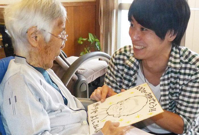 일본 미에현에 있는 요양원에 입소한 노인(왼쪽)에게 한 청년 자원봉사자가 자신이 그린 초상화를 선물하고 있다.