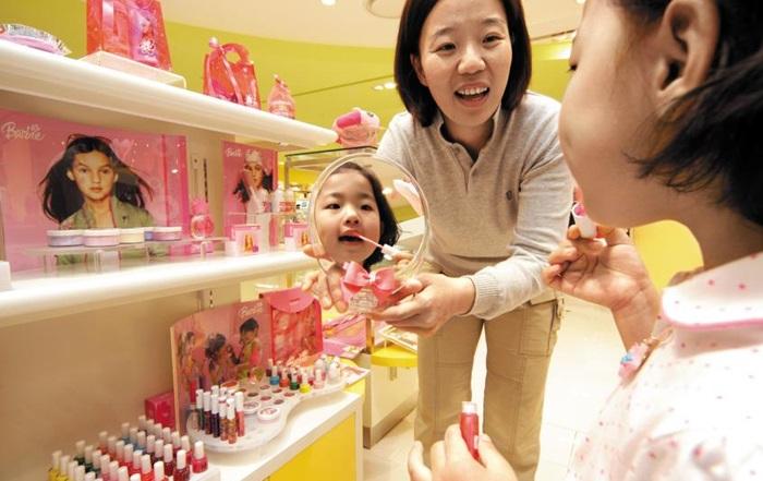 부산 한 백화점 키즈 화장품 코너에 들른 여자 어린이가 입술에 립스틱을 칠하는 모습. 최근에는 청소년 화장의 시작 시기가 초등학교 4~6학년이라는 연구 결과도 나왔다.