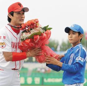 2009년 500도루·1000득점·2500루타를 달성한 이종범(왼쪽)에게 이정후가 꽃다발을 건네는 장면.