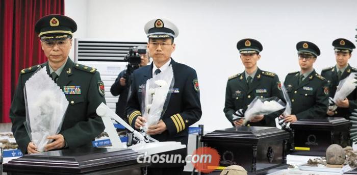 중국군 관계자들이 20일 인천시 육군 17사단에 마련된 '중국군 유해임시안치소'에서 유해 입관식을 앞두고 헌화를 하고 있다. 이날 입관식을 마친 유해 28구는 22일 중국 측에 넘겨진다.