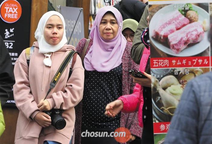 """""""먹을 게 없어요"""" - 지난 22일 동남아의 무슬림 관광객들이 서울 명동 거리를 거닐고 있다. 서울에서 이슬람 율법에 따라 '할랄' 인증을 받은 음식점은 이태원 등지의 8곳뿐이다. 일반 음식점도 메뉴가 중국어 안내 위주이고 영어가 잘 통하지 않아 무슬림 관광객들이 마땅한 먹을거리를 찾는 데 애를 먹고 있다."""