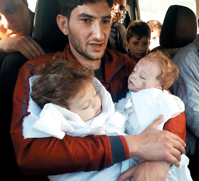 지난 4일(현지 시각) 새벽 시리아 정부군 소속으로 추정되는 전투기의 화학무기 공습으로 9개월 된 쌍둥이를 잃은 압델 하미드 알 유세프씨가 흰 강보에 싸인 아이들의 시신을 끌어안고 침통한 표정을 짓고 있다. 그는 이번 화학무기 공격으로 두 아이와 아내를 포함해 가족과 친척 20여 명을 잃었다.