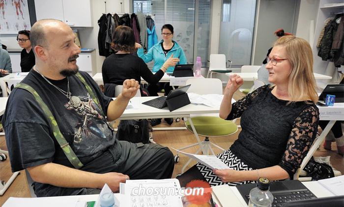 간호조무사 교육 받는 50대 해고자 - 핀란드 코우볼라시(市) 성인교육센터에 개설된 '간호 실무' 수업에서 실파(56·오른쪽)씨가 병원에서 자주 쓰이는 수화(手話) 연습을 하고 있다. 지난해 30년 가까이 다니던 제지 공장에서 해고된 그는 지난 2월부터 간호조무사가 되기 위한 직업훈련을 받고 있다.