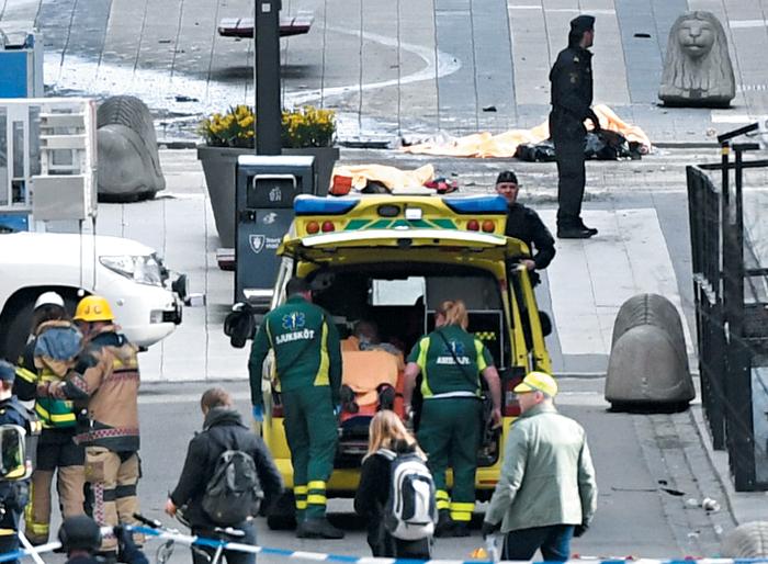 처참한 현장 - 7일(현지 시각) 대형 트럭 한 대가 스웨덴 수도 스톡홀름 중심부의 아흘렌스 백화점으로 돌진해 최소 3명이 사망한 사건이 발생한 직후 현장에 도착한 구급대원이 부상자들을 이송하고 있다. 구급차 뒤로 트럭에 치여 쓰러진 사람들이 쓰러져 있다.
