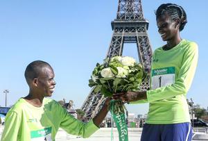 같은 날 파리 마라톤 정상에 오른 케냐 마라토너 부부. 남편 폴 로냔가타(왼쪽)가 아내 푸리티 리오노리포에게 파리의 상징인 에펠탑 앞에서 꽃을 선물했다.