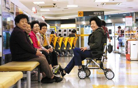 장을 보던 할머니들이 화장품 매장 앞에 모여 담소를 나누고 있다.