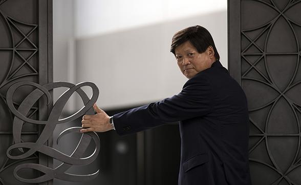 루이까또즈 전용준 회장(64세)이 논현동의 컨템포러리 아트센터 '플랫폼 엘'에서 루이까또즈 브랜드 심벌이 달린 문을 힘껏 밀어젖히고 있다./사진=김지호 기자