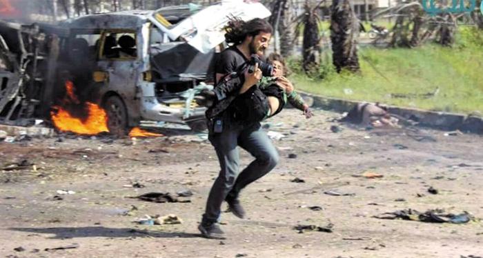 지난 15일(현지 시각) 시리아 북부 알레포에서 발생한 폭탄 테러 현장에서 시리아 사진기자 압둘 카디르 하바크가 오른손에 카메라를 쥔 채 부상한 아이를 들고 응급차로 뛰어가고 있다.