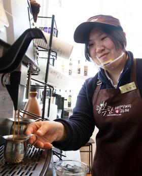SPC그룹 정직원이 된 지적장애 3급 장애인 김현아씨가 행복한 베이커리&카페에서 커피를 내리고 있다.