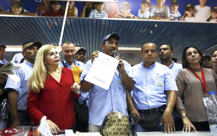 """공장 몰수 소식 전하는 노조원 - 20일(현지 시각) 베네수엘라 발렌시아에 있는 GM 공장의 노조원이 다른 직원들에게 공장 몰수 소식을 전하고 있다. GM 측은 """"공장 문을 닫고 베네수엘라에서 철수하겠다""""고 밝혔다."""