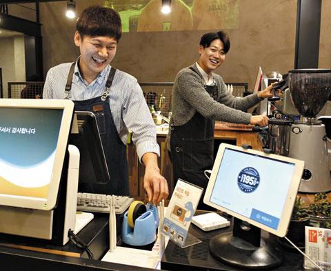 쿠폰·포인트 적립 서비스업체 스포카와 제휴를 맺은 매장에서 종업원이 고객의 전화번호를 입력해 고객에게 포인트를 적립해주고 있다.