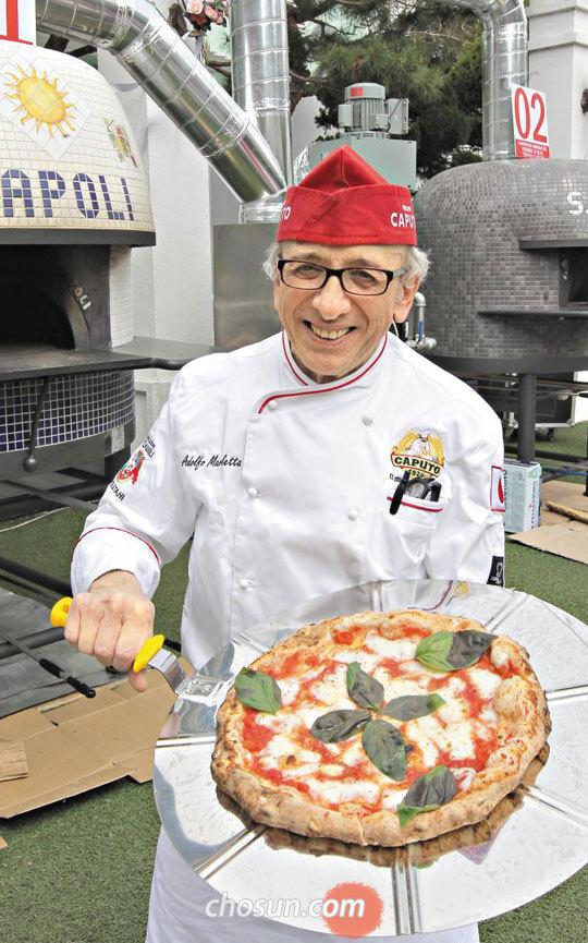 '나폴리 피자 장인 한국선수권대회'심사위원장을 맡은 피자 장인 아돌포 마를레타씨가 자신이 만든 정통 나폴리 피자를 들고 있다.