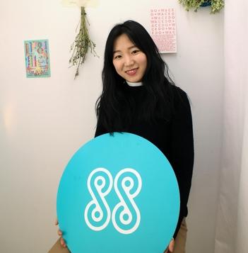 윤자영 스타일쉐어 대표가 단추 모양의 브랜드 심볼과 함께 포즈를 취했다. 옷감과 옷감을 연결하는 단추는 스타일쉐어의 근간인 '소통'을 상징한다./사진=스타일쉐어 제공