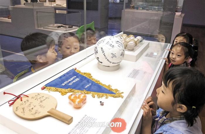 지난달 27일 경기도 수원광교박물관을 찾은 어린이들이 '소강 민관식실'에서 선수들의 사인이 적힌 탁구채와 공 등 여러 기증품을 관람하고 있다.