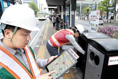 16일 경기도 고양시의 한 버스 정류장에서 고양시 관계자들이 태블릿을 이용해 쓰레기통 안에 쌓인 쓰레기양을 확인하고 있다.