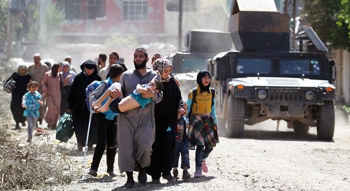 """17일(현지 시각) 이라크군과 이슬람국가(IS) 대원들이 전투를 벌인 이라크 모술 서부 지역에서 주민들이 피란길에 오르고 있다. 야히야 라술 이라크군 대변인은 전날 기자회견에서 """"IS의 최대 근거지 모술 서부를 90% 정도 탈환했다""""고 밝혔다."""