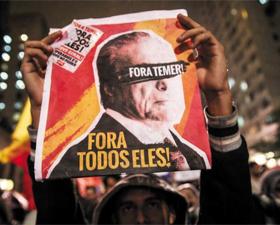 18일(현지 시각) 브라질 상파울루에서 탄핵 위기에 몰린 미셰우 테메르 대통령의 퇴진을 요구하는 시위가 열린 가운데 한 시민이 테메르 대통령 사진에 '퇴진하라'라는 문구가 적힌 피켓을 들고 있다.
