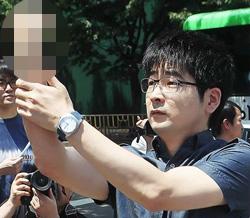 탁현민씨가 2011년 7월 MBC 앞에서 '주먹 욕'을 하고 있다.