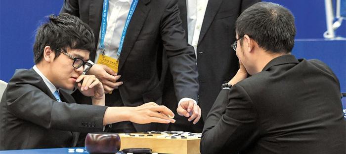 대국 종료 후 커제(왼쪽 앉은이)가 동료 기사들에게 둘러싸여 복기하는 모습. 커제는 155수 만에 백 불계로 허망하게 무너졌다.