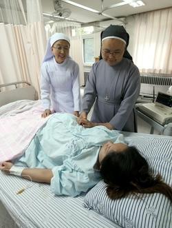 환자의 손을 어루만지는 도티병원 원장 권 글라라 수녀./사진=박상훈 기자