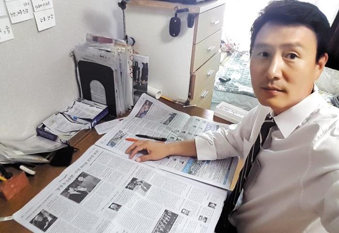 정일용(43)씨가 갓 배달된 조선일보를 책상 위에 펴 놓고 꼼꼼히 살피고 있다.