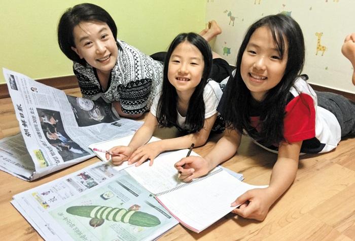 복성현씨의 아내 이은아(38)씨가 두 딸과 함께 방바닥에 엎드린 채 신문을 보며 즐거워하고 있다.