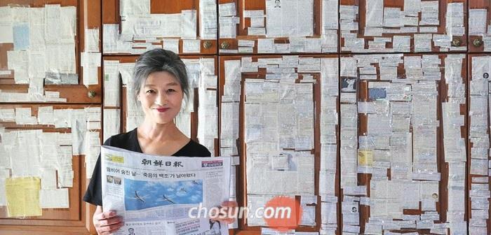 독자 임수련(57)씨가 지난 2년간 주방 벽에 붙여 놓은 조선일보 기사 스크랩 앞에서 활짝 웃고 있다.