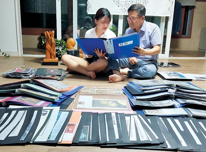 최규식(60)씨가 조선일보 시사 관련 기사를 모은 스크랩북을 대학생인 딸 수현(19)씨와 함께 보고 있다. 거실 바닥에는 최씨가 20여 년 동안 모아온 조선일보 기사들이 펼쳐져 있다.